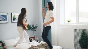 Hombre y mujer que se divierten que toca la guitarra que canta en el baile teledirigido en cama almacen de metraje de vídeo