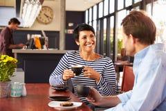Hombre y mujer que se encuentran sobre el café en un restaurante Imagenes de archivo