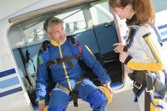 Hombre y mujer que se preparan para la experiencia que se lanza en paracaídas Imagenes de archivo