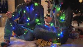 Hombre y mujer que se sientan cerca de árbol del Año Nuevo con una guirnalda alrededor del cierre del cuello para arriba Guirnald almacen de video