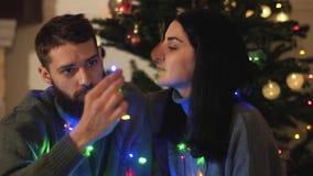 Hombre y mujer que se sientan cerca de árbol del Año Nuevo con una guirnalda alrededor del cuello Pelo de su novio, beso de la ca metrajes