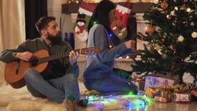 Hombre y mujer que se sientan cerca del árbol de navidad en sitio moderno Juguetes colgantes de la muchacha, hombre que toca la g almacen de metraje de vídeo