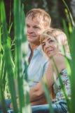 Hombre y mujer que se sientan en alta hierba Foto de archivo libre de regalías