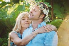 Hombre y mujer que se sientan en alta hierba Imagen de archivo libre de regalías