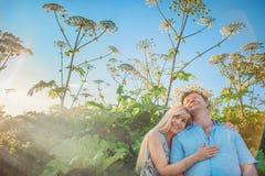 Hombre y mujer que se sientan en alta hierba Foto de archivo
