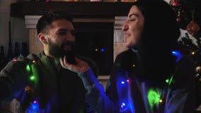 Hombre y mujer que se sientan en el árbol de navidad con una guirnalda La muchacha que rasguña la barba del hombre, sonrisa de am almacen de video