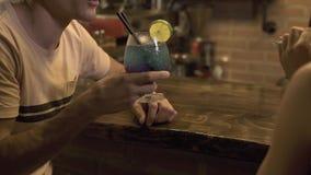 Hombre y mujer que se sientan en el contador de la barra y el cóctel alcohólico de consumición mientras que iguala la fecha en ca almacen de video