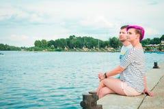 Hombre y mujer que se sientan en la orilla del río Fotos de archivo libres de regalías