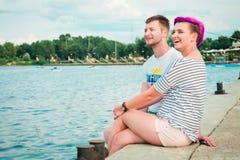 Hombre y mujer que se sientan en la orilla del río Imágenes de archivo libres de regalías