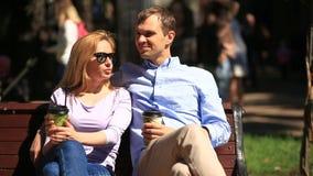 Hombre y mujer que se sientan en un banco Un hombre y una mujer hermosa una fecha Beben el café y hablan almacen de metraje de vídeo
