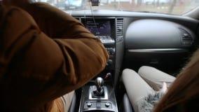Hombre y mujer que se sientan en un coche mientras que conduce El hombre está bebiendo un poco de bebida Tablero de instrumentos  almacen de video
