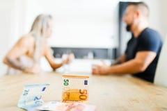 Hombre y mujer que se sientan por la tabla en lado opuesto y que discuten - dinero imagenes de archivo