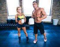 Hombre y mujer que sostienen el envase con la nutrición de los deportes Imagenes de archivo