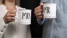 Hombre y mujer que sostienen las tazas Sr. y señora almacen de metraje de vídeo