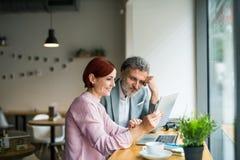 Hombre y mujer que tienen reunión de negocios en un café, usando el ordenador portátil fotografía de archivo libre de regalías