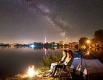 Hombre y mujer que tienen un resto en orilla debajo del cielo nocturno fotografía de archivo