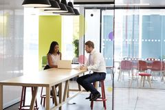 Hombre y mujer que tienen una reunión informal en el trabajo foto de archivo libre de regalías