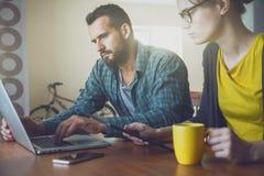 Hombre y mujer que trabajan así como el ordenador portátil imagen de archivo libre de regalías