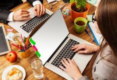 Hombre y mujer que trabajan en los ordenadores portátiles Imágenes de archivo libres de regalías