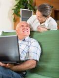 Hombre y mujer que usa el ordenador portátil en casa Foto de archivo