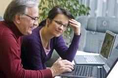 Hombre y mujer que usa las computadoras portátiles fotos de archivo