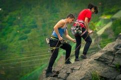 Hombre y mujer rapelling abajo de la montaña Imagenes de archivo