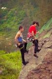 Hombre y mujer rapelling abajo de la montaña Fotos de archivo libres de regalías
