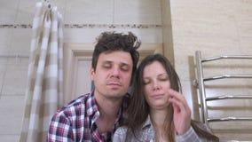Hombre y mujer soñolientos de los pares en el cuarto de baño con la resaca que intenta despertar y la sonrisa almacen de video