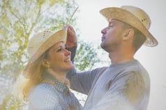 Hombre y mujer sonrientes al aire libre en los sombreros de paja que miran a cada ot Foto de archivo libre de regalías