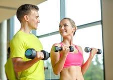 Hombre y mujer sonrientes con pesas de gimnasia en gimnasio Imágenes de archivo libres de regalías