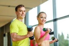 Hombre y mujer sonrientes con pesas de gimnasia en gimnasio Imagenes de archivo