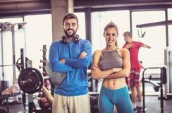 Hombre y mujer sonrientes en gimnasio foto de archivo