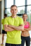 Hombre y mujer sonrientes en gimnasio Foto de archivo libre de regalías