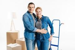 Hombre y mujer sonrientes que abrazan por el carro de la entrega y las cajas de cartón de mudanza imágenes de archivo libres de regalías