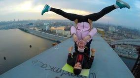 Hombre y mujer sonrientes que hacen los trucos acrobáticos en el puente, drogadictos de la yoga de la adrenalina almacen de metraje de vídeo
