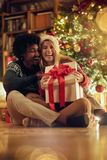 Hombre y mujer sonrientes que intercambian regalos de Navidad imagen de archivo
