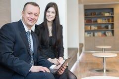 Hombre y mujer sonrientes que se sientan con un ordenador portátil Foto de archivo libre de regalías