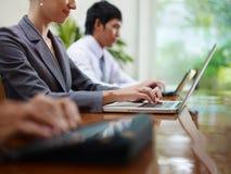 Hombre y mujeres de negocios que pulsan en la PC durante la reunión Imagen de archivo libre de regalías