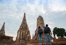 Hombre y mujeres del viajero con la mochila que caminan en el templo Ayuttaya Imágenes de archivo libres de regalías