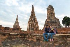 Hombre y mujeres del viajero con la mochila que caminan en el templo Ayuttaya, Tailandia Imagen de archivo libre de regalías