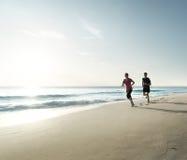 Hombre y mujeres que corren en la playa tropical en la puesta del sol Foto de archivo libre de regalías