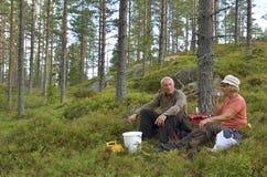 Hombre y mujeres que se sientan en la tierra Foto de archivo