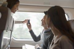 Hombre y mujeres sonrientes jovenes que usan el teléfono en un tren, Pekín Fotografía de archivo