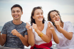 Hombre y mujeres sonrientes que bailan sentarse en la playa Fotografía de archivo libre de regalías