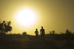 Hombre y niño con el perro en la puesta del sol Imágenes de archivo libres de regalías
