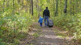 Hombre y niño con una maleta que caminan en una trayectoria de bosque metrajes