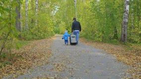 Hombre y niño con una maleta que caminan en una trayectoria de bosque almacen de video