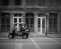Hombre y niño pequeño que montan un carro del golfo Imagen de archivo libre de regalías