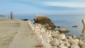 Hombre y pequeña 'promenade' de la mañana de la playa del beagle metrajes