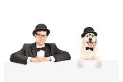 Hombre y perro con los sombreros que presentan detrás del panel Imágenes de archivo libres de regalías